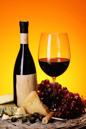 Refined still life of wine, cheese and grapes on wicker tray on wooden table on orange background photo