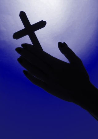 Female hands with crucifix, on bright blue background photo