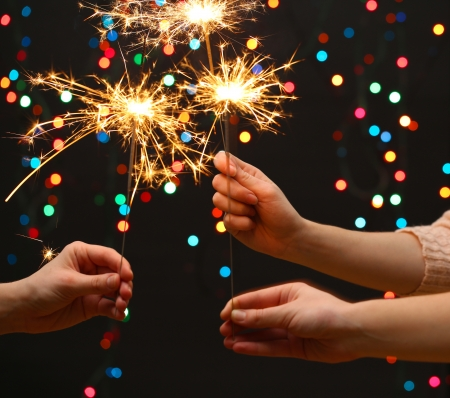 new years eve: beautiful sparklers in woman hands on garland background