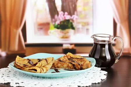 Sweet pancakes on plate with condensed milk on table in room Stock Photo - 18717547