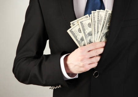 Business man hiding money in pocket on grey background photo