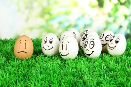 Eggs with funny faces on grass on bright background photo