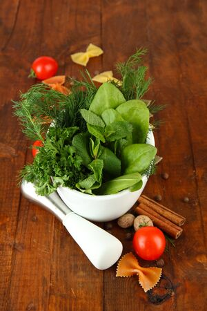 Herbs and spices in ceramic mortar, on wooden background photo