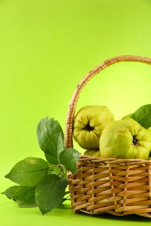 sweet quinces with leaves in basket, on green background photo