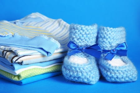 baby clothes: Pile of baby clothes on blue background