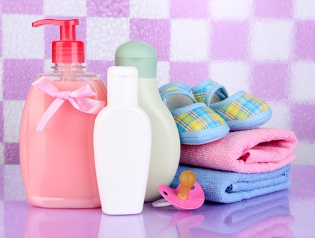 Baby cosmetics and towels  in bathroom on violet tile wall background Stock Photo - 18741174
