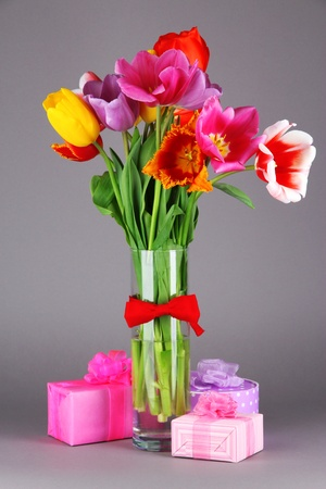 Beautiful tulips in bouquet with gifts on gray background photo