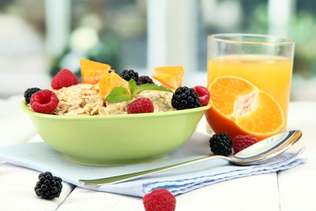 prepared food: tasty oatmeal with berries and glass of juice on table, on window background
