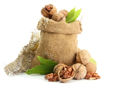 walnuts with green leaves in  burlap bag, isolated on white photo
