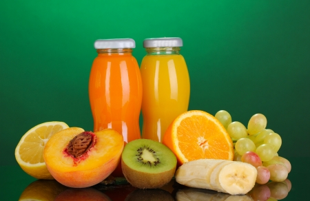 Delicious multifruit juice in a bottle and fruit next to it on green background photo