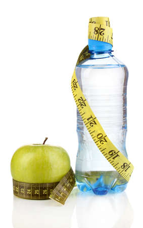 Bottle of water, apple and measuring tape isolated on white photo