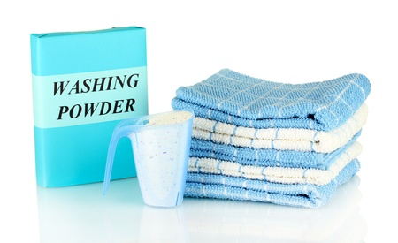 Box of washing powder with blue measuring cup and towels, isolated on white photo