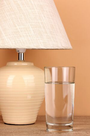 table lamp and glass of water on beige background photo