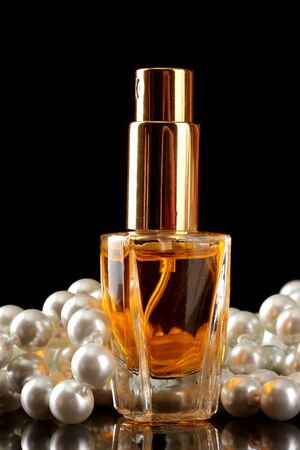 womens perfume in beautiful bottle and beads, on black background photo