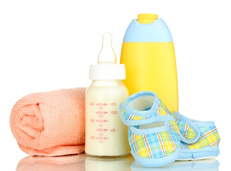 Bottle of milk, pacifier, shampoo and towel isolated on white photo