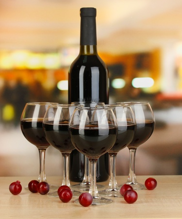 Red wine in glass and bottle on room background photo