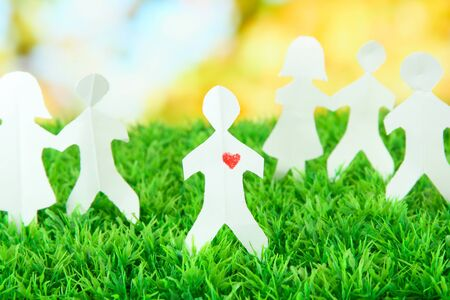 Paper people on green grass on bright background Stock Photo - 18775790