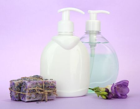 Liquid and hand-made soaps on purple background photo