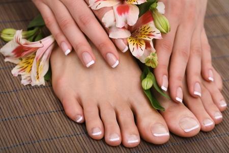 Beautiful woman legs et les mains sur la natte de bambou