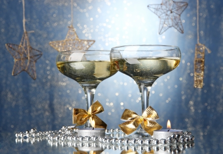 Two glasses of champagne on bright background with lights photo