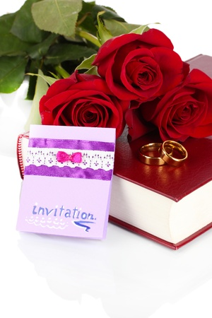 Wedding rings with roses and greeting card on bible isolated on white photo