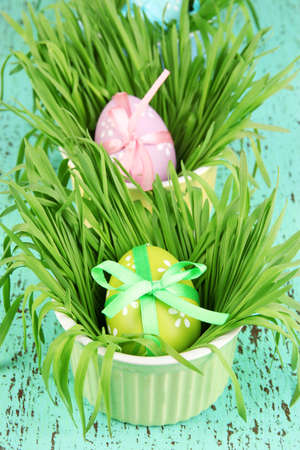 Easter eggs in bowls with grass on green wooden table close up photo