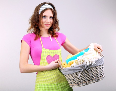 washing clothes: Housewife carrying laundry basket full of clothing on grey background Stock Photo