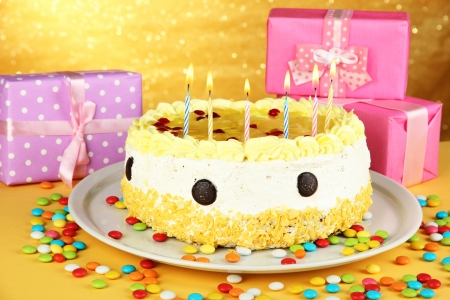 Happy birthday cake and gifts, on yellow background photo