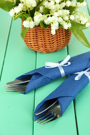 Fork and knife wrapped in blue paper napkin, on color wooden background Stock Photo - 18816315