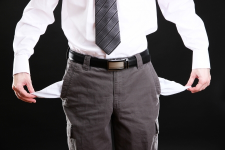 Business man showing his empty pockets, on black background photo