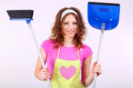 Young housewife with broom and dustpan on grey background photo