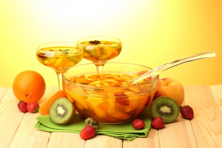 bowl: punch in bowl and glasses with fruits, on wooden table, on yellow background