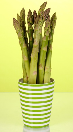 nutritiously: Fresh asparagus in colorful pot on green background