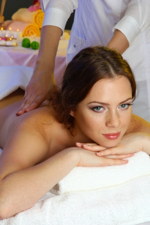 beautiful young woman in spa salon getting massage, isolated on white photo