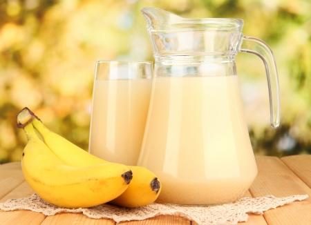 Full glass and jug of banana juice and bananas on wooden table outdoor photo