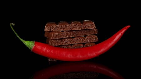 Dark chocolate with chili pepper, isolated on black photo