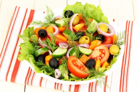 Fresh salad in plate on wooden table photo