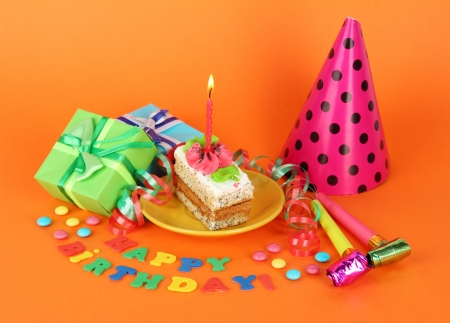 Colorful birthday cake with candle and gifts on orange background photo