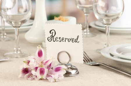 formal dinner: Reserved sign on restaurant table with empty dishes and glasses