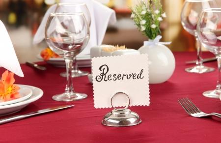 reservacion: Reservados se�al en la mesa de restaurante con platos y vasos vac�os