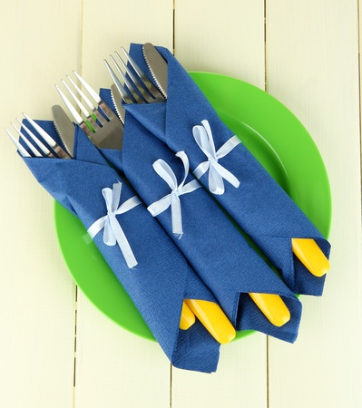Forks and knives wrapped in blue paper napkins, on color wooden background Stock Photo - 18848210