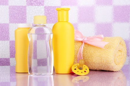 Baby cosmetics and towel in bathroom on violet tile wall background Stock Photo - 18849451