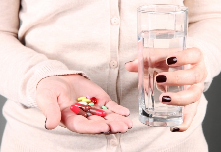 Many pills and glass water in hand Stock Photo - 18848043
