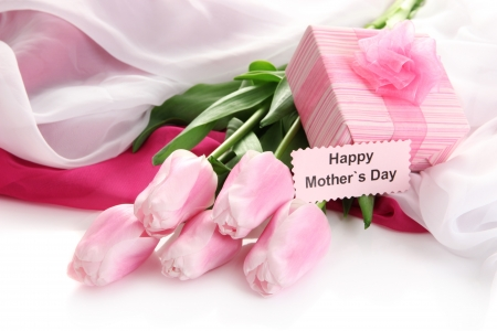 Bouquet of pink tulips and gift on cloth for Mother's Day, isolated on white photo