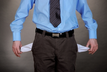 Business man showing his empty pockets, on grey background photo