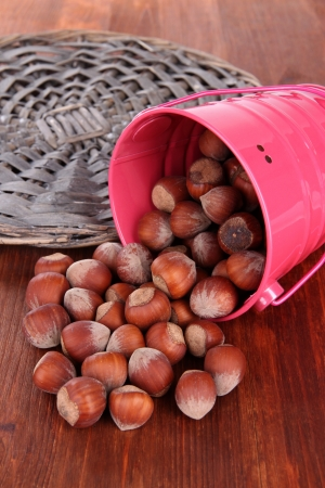Overturned bucket with hazelnuts on wooden background Stock Photo - 18850434