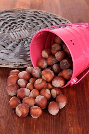 Overturned bucket with hazelnuts on wooden background Stock Photo - 18850434
