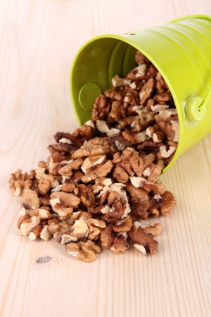 Overturned bucket with nuts on wooden background Stock Photo - 18849986