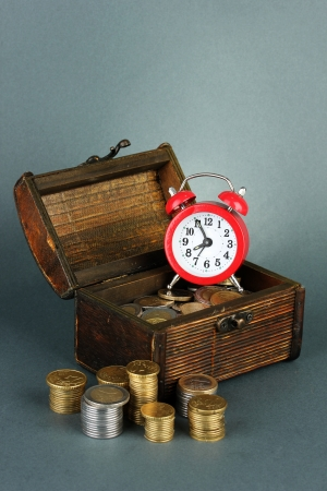 Alarm clock with coins in chest on grey background photo