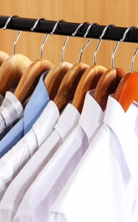 Men's shirts on hangers in wardrobe photo
